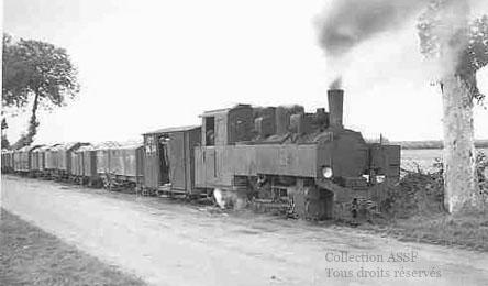 La vaillante 040T N°4-12, sur la ligne métrique Pithiviers-Toury tire un lourd convoi de tombereaux betteraviers dans les années 60. On remarquera l'attelage automatique, servant aussi d'organe de tamponnement, et le wagon de service avec son freineur.