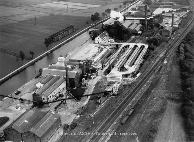 Une vue plus récente du même établissement, côté voies ferrées. Coll. Sylvère Thomas. Sur la rive opposée la piste de halage avec un engin posté à la hauteur du panache de fumée, en haut de l'image.