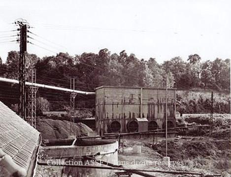 """Réserve d'eau propre de l'usine. Ce grand réservoir en béton circulaire dénommé """"tinette"""" recevait de l'eau pompée à 5 km. de l'usine dans la rivière """"La Savière"""". A l'arrière-plan, les réfrigérants en béton. But : refroidir l'eau chaude des condensats de vapeur de la colonne baromètrique à l'aide de gros ventilateurs."""